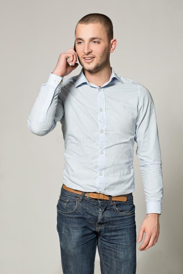 Cool biznesowego mężczyzna opowiada na telefonie komórkowym na szarym tle zdjęcia royalty free