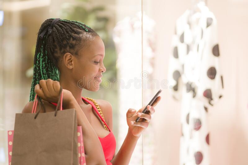 Cool black girl shopping - young happy and beautiful black afro American woman holding shopping bags and mobile phone buying at. Mall fashion store enjoying stock image