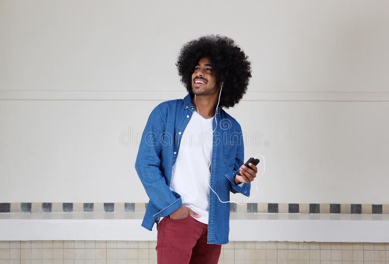 Cool black guy listening to music on mobile phone stock photo