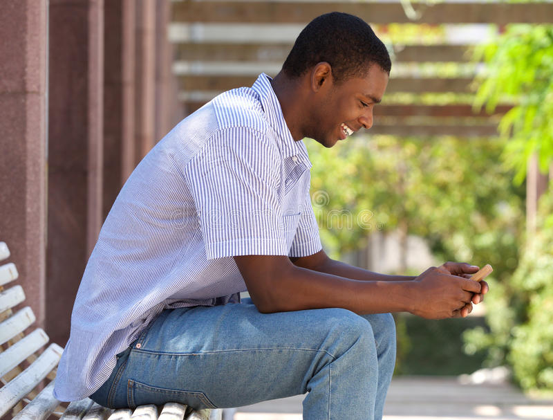 Cool black guy looking at cell phone royalty free stock image