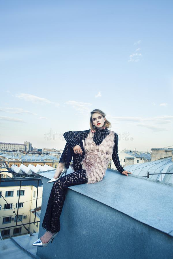 Cool blond real fashion style girl posing sensual on roof top, lifestyle people concept. Closeup stock photo