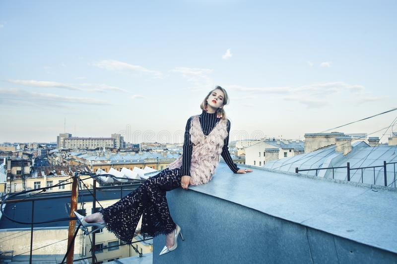 Cool blond real fashion style girl posing sensual on roof top, lifestyle people concept. Closeup royalty free stock image