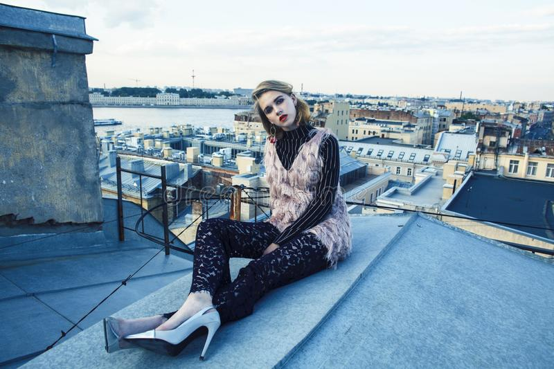 Cool blond real fashion style girl posing sensual on roof top, lifestyle people concept. Closeup royalty free stock images