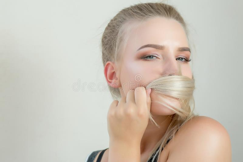 Cool blonde model covering her mouth by hair, posing on a grey royalty free stock photos