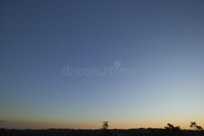Cool blue sunset in desert with tree silhouettes royalty free stock photo