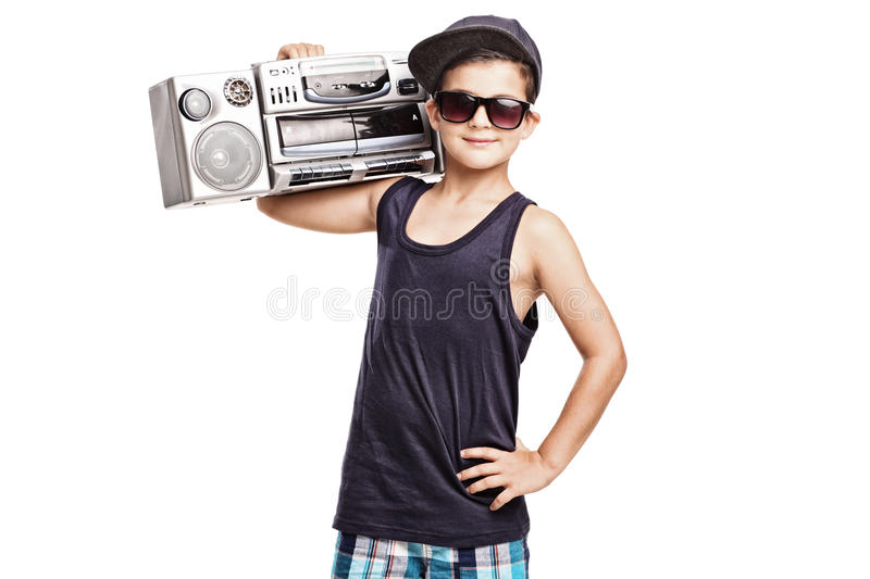 Cool boy in hip hop outfit holding a ghetto blaster. Over his shoulder and looking at the camera isolated on white background royalty free stock photography