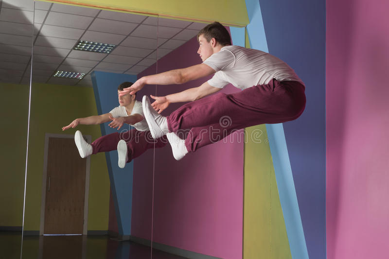 Cool break dancer mid air doing the splits in front of mirror stock images