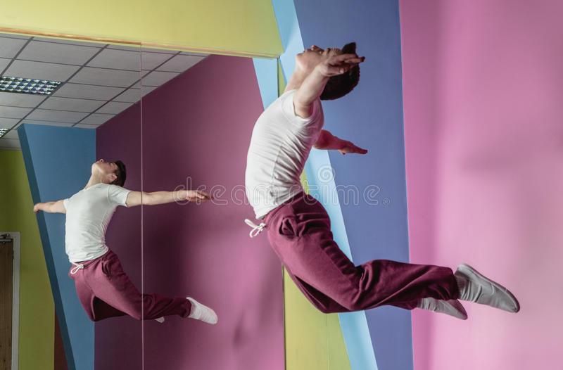 Cool break dancer mid air in front of mirror royalty free stock photography