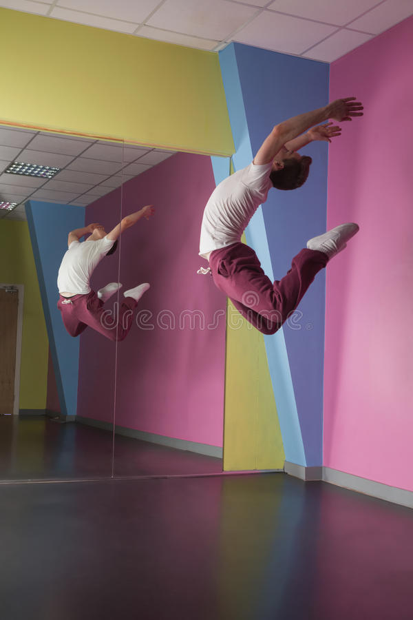 Cool break dancer mid air in front of mirror stock photography