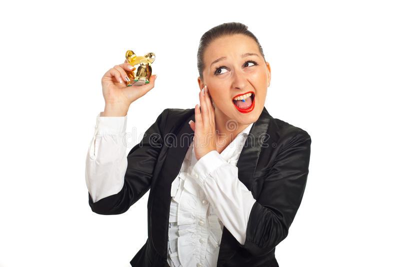 Cool business woman tryind to hear piggy bank stock images