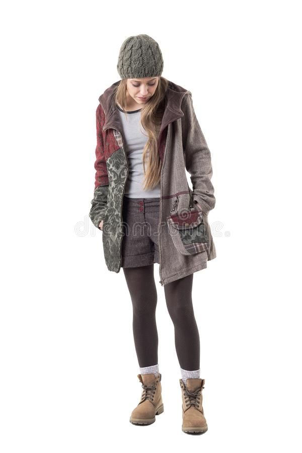 Cool candid young hipster style woman in warm winter coat and woolly cap looking down. stock images