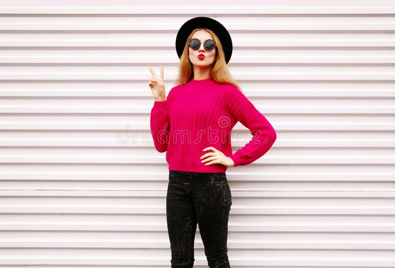 cool cheerful girl blowing red lips sending sweet air kiss in colorful pink knitted sweater, black round hat stock photo