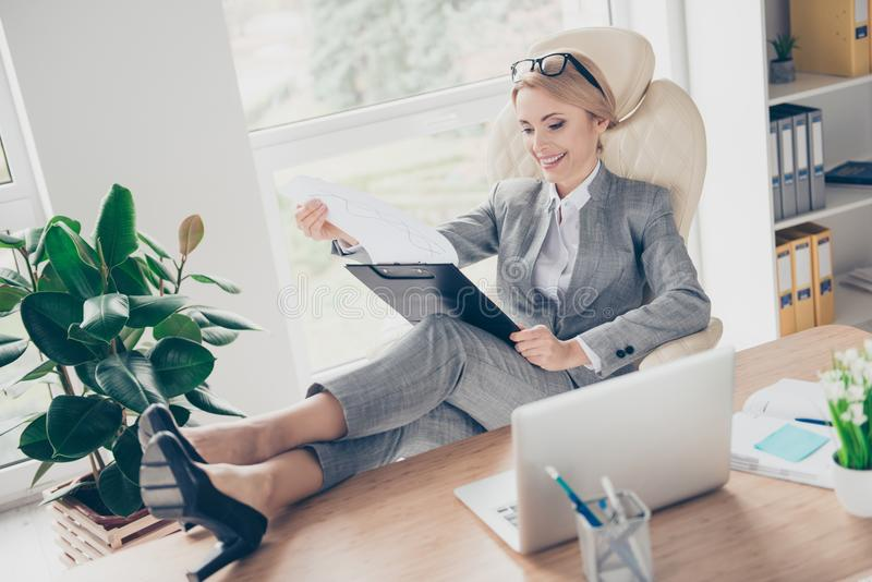 Cool, cheerful, smiling woman hold legs on table, sitting comfortable on chair at desk in work station, having clipboard in hands. Expertising monthly report royalty free stock images