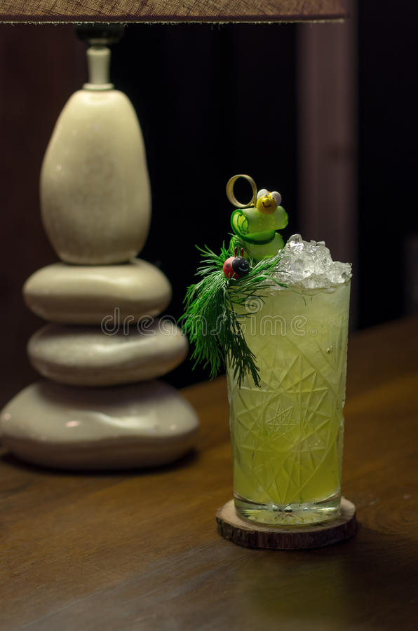 Cool cocktail with cucumber and parsley. Cold cocktail with cucumber and parsley decorated with bee and ladybug royalty free stock image