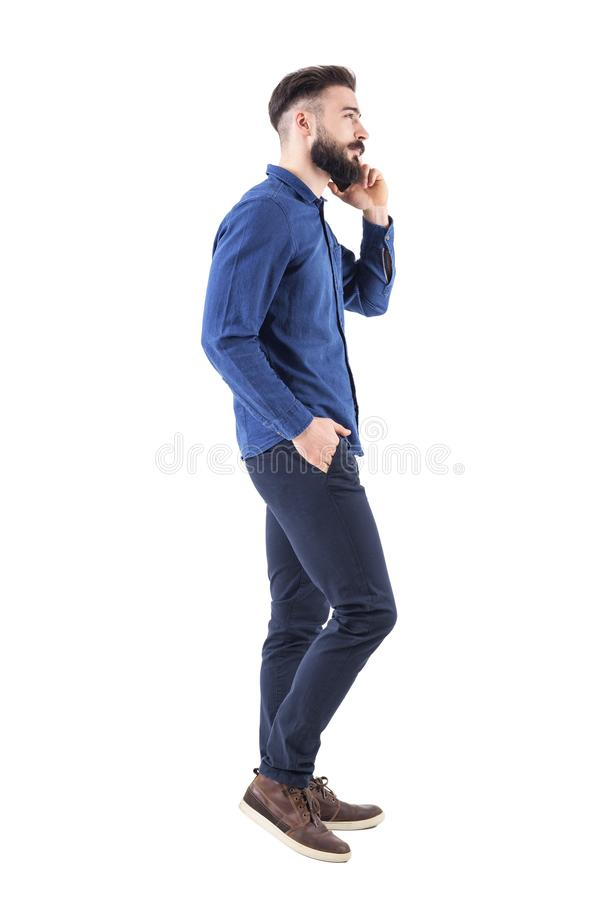 Cool confident bearded well dressed guy talk on the phone walking with one hand in pocket royalty free stock images