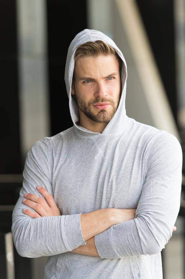 Cool and confident. Man unshaven hooded folded arms looks handsome and cool. Guy bearded attractive cares about. Appearance. Man bristle serious face, urban royalty free stock photography