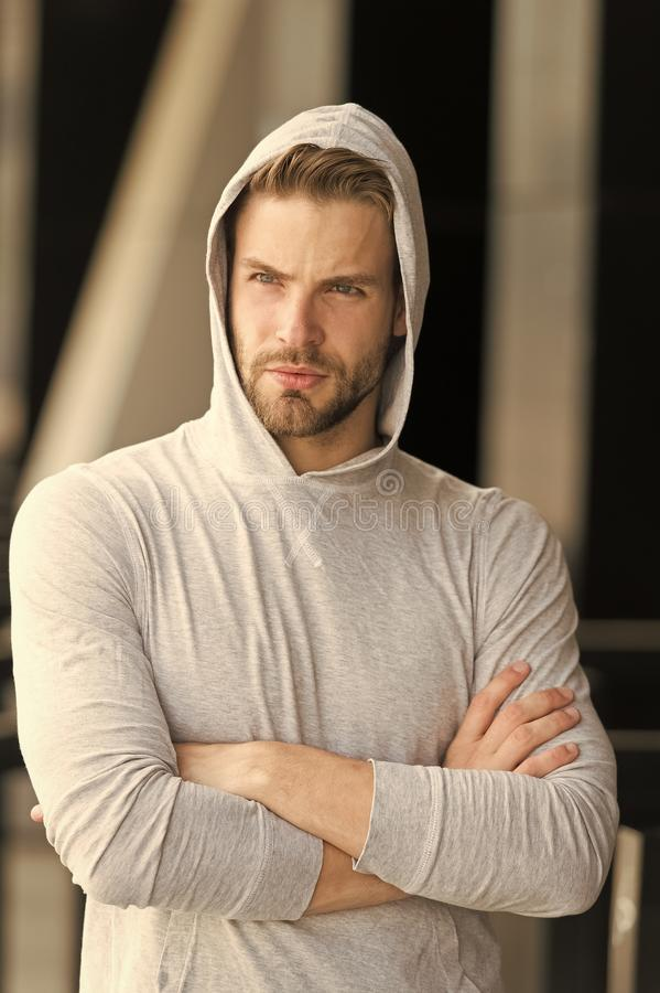 Cool and confident. Man unshaven hooded folded arms looks handsome and cool. Guy bearded attractive cares about. Appearance. Man bristle serious face, urban stock images