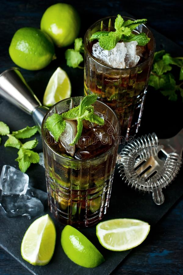Cool  Cuba libre  in glasses on  dark table, holidays party concept stock image