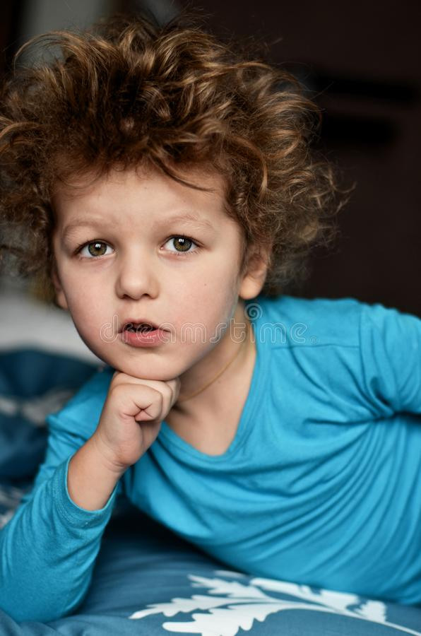 Cool curly-haired boy lies on the bed and propped his head on his fist stock images