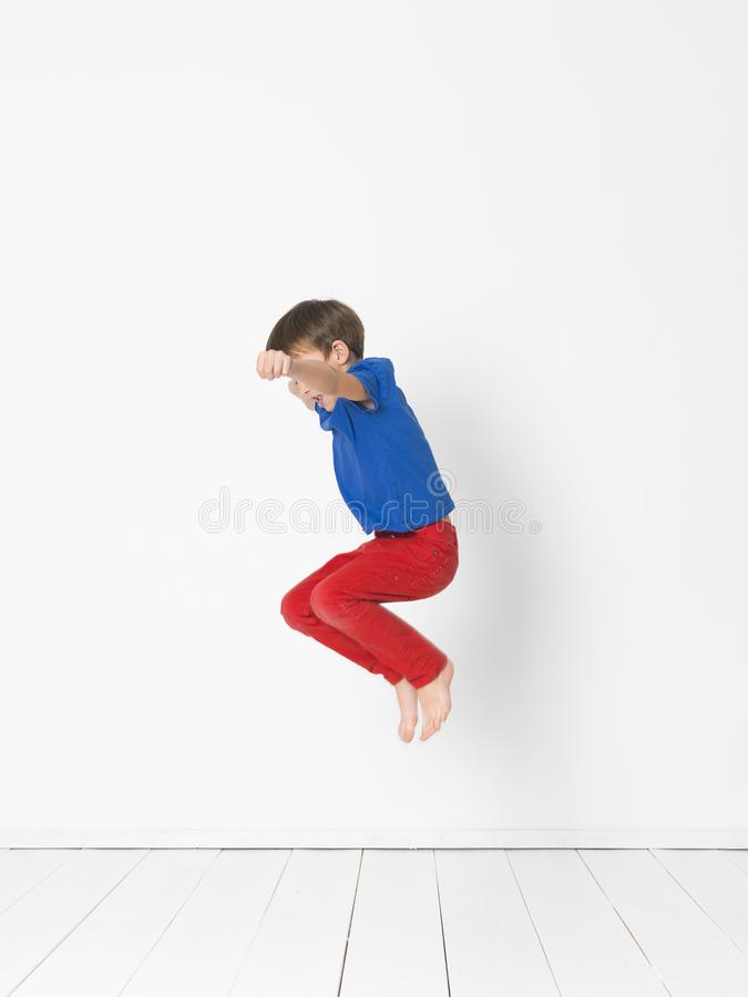 Cool, cute boy with blue shirt and red trousers is jumping high in the studio in front of white background and white wooden floor royalty free stock image
