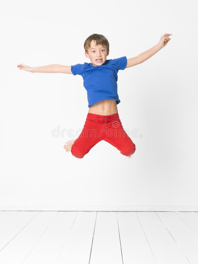 Cool, cute boy with blue shirt and red trousers is jumping high in the studio in front of white background and white wooden floor stock photos