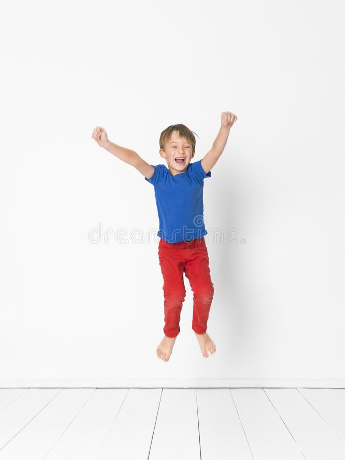 Cool, cute boy with blue shirt and red trousers is jumping high in the studio in front of white background and white wooden floor. And is having fun stock photos