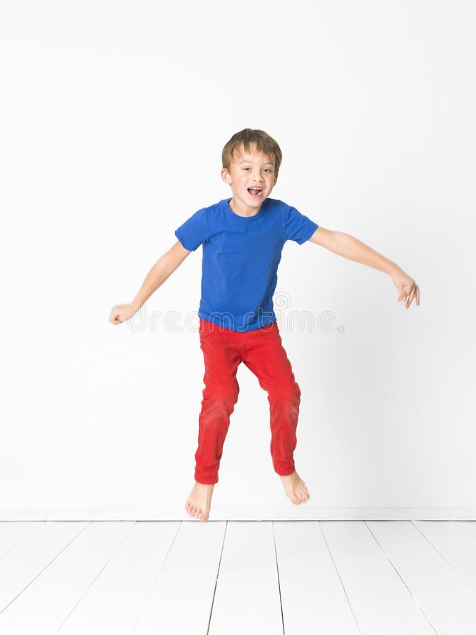 Cool, cute boy with blue shirt and red trousers is jumping high in the studio in front of white background and white wooden floor royalty free stock images