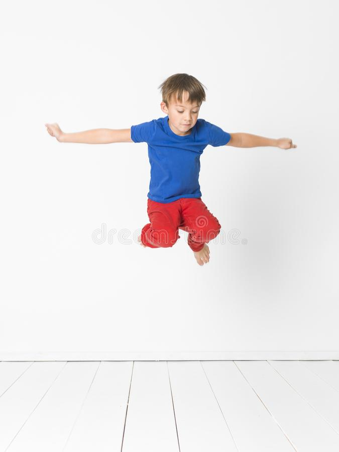 Cool, cute boy with blue shirt and red trousers is jumping high in the studio in front of white background and white wooden floor royalty free stock photography