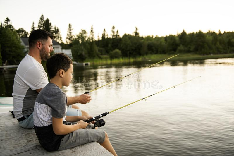 Cool Dad and son fishing on lake royalty free stock photography