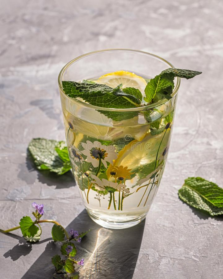 A cool drink that quenches thirst on a hot day with melissa and lemons with a glass pattern with a summer pattern. Shot from close royalty free stock photography