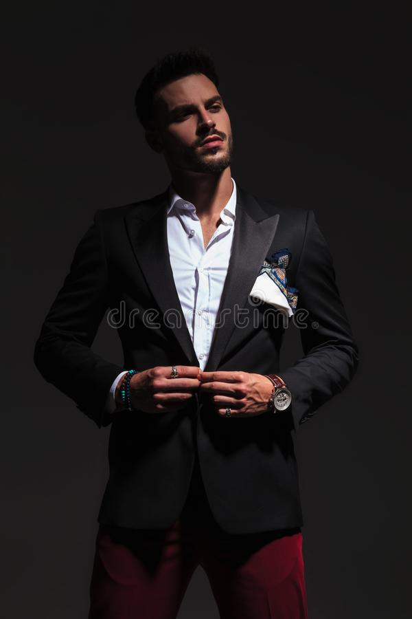 Cool elegant young man buttoning his suit and looks away stock images