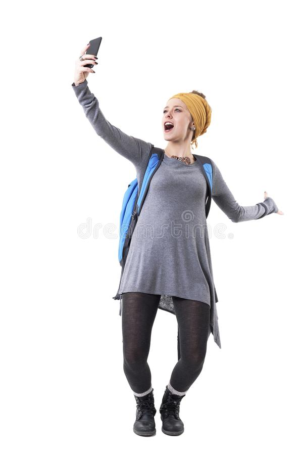 Cool excited cheerful young hipster backpacker traveler woman taking photo memories with mobile phone. stock images