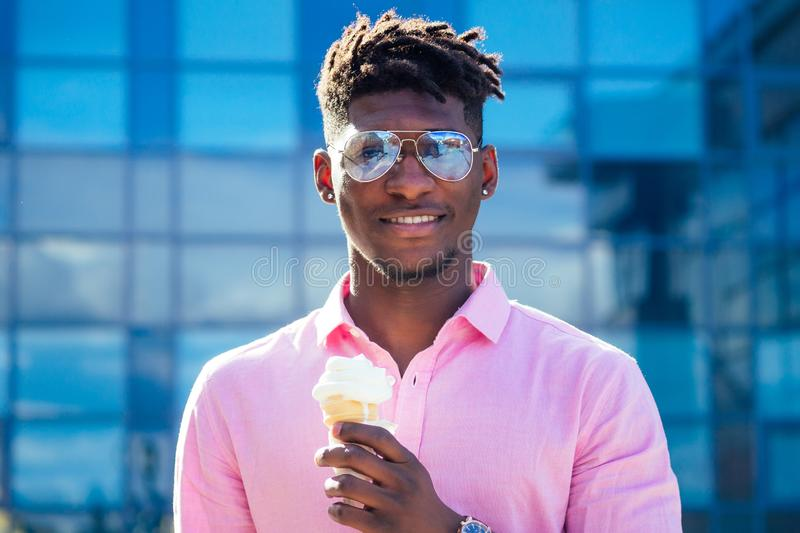 Cool and fashionable African American guy dreadlocks hair in sunglasses eating ice cream in a waffle horn in the summer. In the park royalty free stock photos