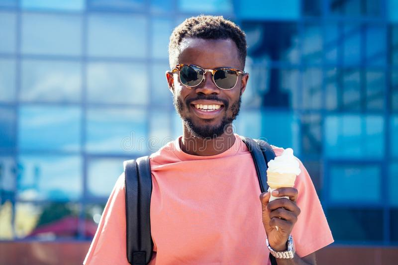 Cool and fashionable African American guy in sunglasses eating ice cream in a waffle horn in the summer in the park.  royalty free stock image