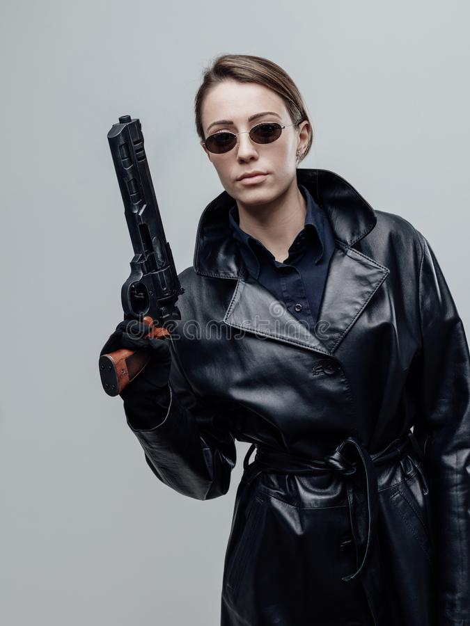 Cool female spy holding a gun royalty free stock photography