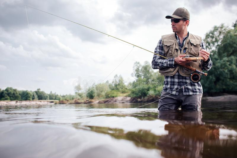 Cool fisherman stands in water and looks straight forward. He is serious. Guy holds fly rod and wooden box of artificial royalty free stock photos