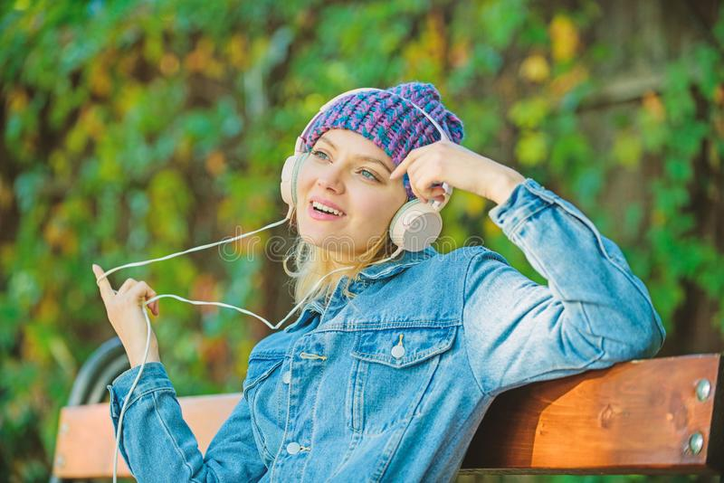 Cool funky girl enjoy music in headphones outdoor. Girl listen music in park. Melody sound and mp3. Music fan concept. Headphones must have modern gadget royalty free stock image