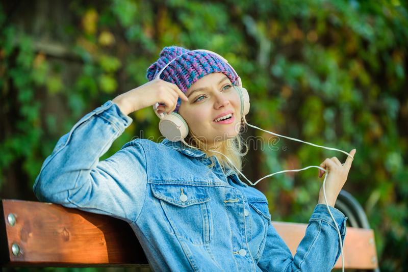 Cool funky girl enjoy music in headphones outdoor. Girl listen music in park. Melody sound and mp3. Music fan concept. Headphones must have modern gadget royalty free stock images