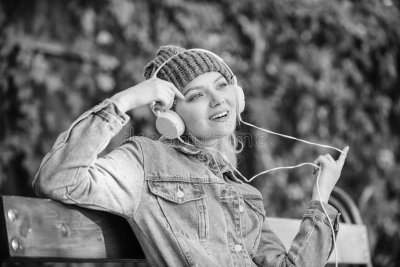 Cool funky girl enjoy music in headphones outdoor. Girl listen music in park. Melody sound and mp3. Music fan concept. Headphones must have modern gadget stock photography