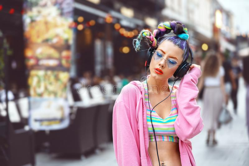 Cool funky young hipster woman with trendy eyeglasses and crazy hair listening music on headphones outdoor. Cool funky young woman with trendy eyeglasses stock photos