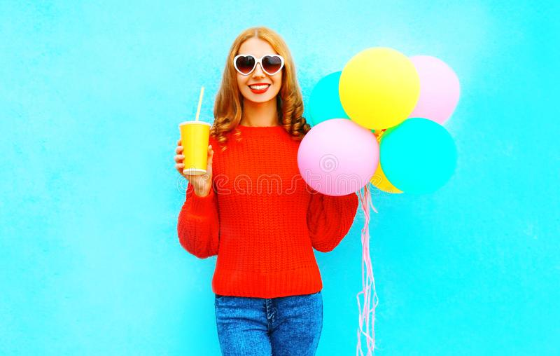 Cool funny girl with an air balloons holds cup of fruit juice stock photography