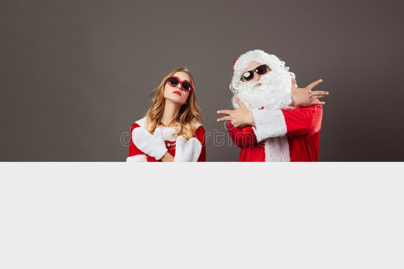 Cool gangsta Santa Claus and young beautiful mrs. Claus in sunglasses stand behind a white canvas on the gray background stock images