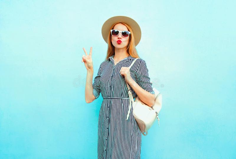 Cool girl with red lips sending sweet air kiss in summer round straw hat with backpack on blue stock photo
