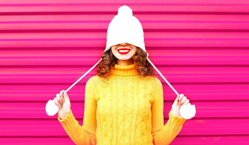 Cool girl wearing a colorful knitted yellow sweater. Over pink background royalty free stock photo