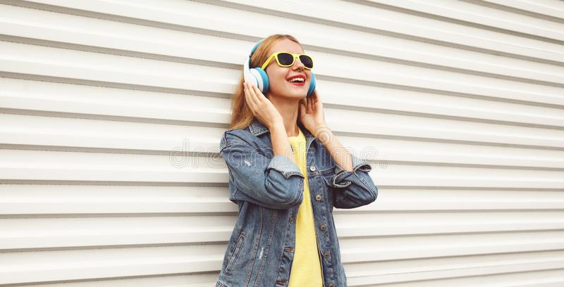 Cool girl in wireless headphones enjoying listening to music on city street over white wall. Background stock image