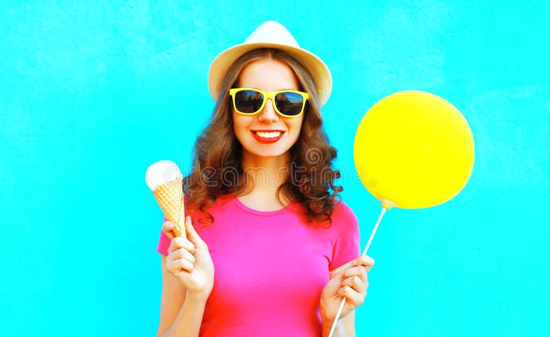 Cool girl with yellow air balloon and ice cream cone. Coo girl with yellow air balloon and ice cream cone wearing straw hat and pink t-shirt over colorful blue royalty free stock image
