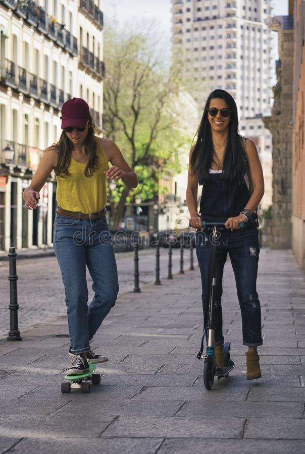 Cool girls couple riding scooter and skate, modern friendship concept royalty free stock photos
