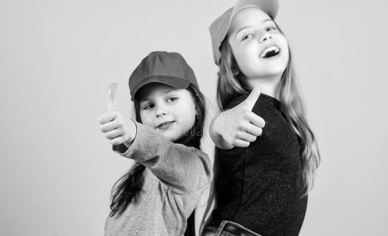 Cool girls. Little cute girls wearing bright baseball caps. Modern fashion. Hats and caps. Stylish accessory. Kids stock photos
