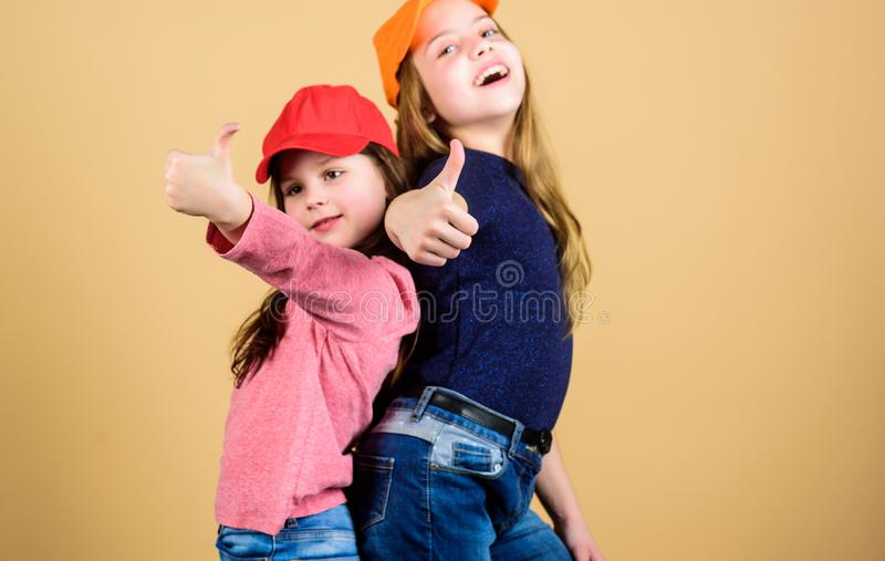 Cool girls. Little cute girls wearing bright baseball caps. Modern fashion. Stylish accessory. Kids fashion. Feeling royalty free stock photos
