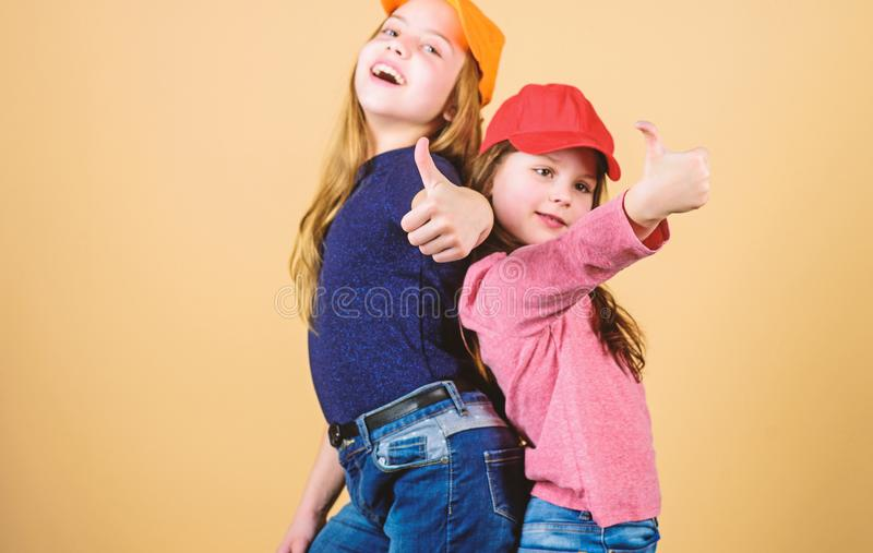 Cool girls. Little cute girls wearing bright baseball caps. Modern fashion. Stylish accessory. Kids fashion. Feeling. Confident wearing caps. Sisters stand back royalty free stock photography